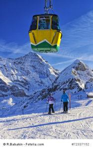 Two girls on ski near cable railway on winter sport resort in sw